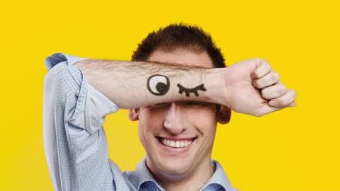 promofoto: man houdt arm met een getekende knipoog voor zijn hoofd